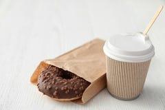Smakowity pączek w papierowej torbie i kawie na drewnianym stole zdjęcie royalty free