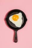 Smakowity piękny jedzenie smażył jajko w niecce na modnym różowym backgr Zdjęcia Royalty Free