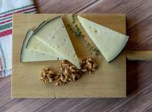 Smakowity ser na nieociosanym stole towarzyszącym zdrowymi obranymi orzechami włoskimi i świeżymi tymiankowymi gałąź obrazy stock