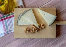 Smakowity ser na nieociosanym stole towarzyszącym zdrowymi obranymi orzechami włoskimi i butelką ekstra dziewicza oliwa z oliwek zdjęcie stock