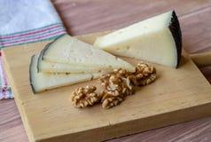 Smakowity ser na nieociosanym stole towarzyszącym zdrowymi obranymi orzechami włoskimi obrazy royalty free