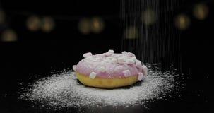 Smakowity ?wie?y p?czek k?a?? na czerni powierzchni i dostaje kropi z lodowacenie cukieru proszkiem zbiory