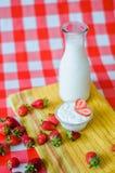 Smakowity zdrowy śniadanie, świeży mleko w szklanej butelce, smakowity jogurt w małym szklanym pucharze z mnóstwo truskawkami wok fotografia royalty free
