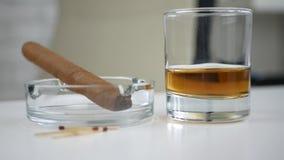 Smaksatt svart röka cigarr i askfat och ett exponeringsglas med whisky på tabellen stock video