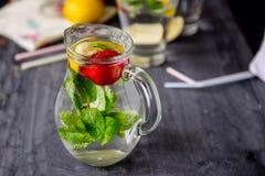 Smaksatt vatten med den nya jordgubbar och mintkaramellen i exponeringsglas skorrar på en svart trätabell med ljusa detaljer Sele Royaltyfria Foton