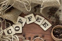 Smaksatta kaffebönor spillde ut ur påsen på en trätabell Royaltyfri Fotografi