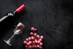 Smaku czerwone wino Butelka czerwone wino, szkło i czerwony winogrono na czarnym tło odgórnego widoku copyspace, Zdjęcia Royalty Free