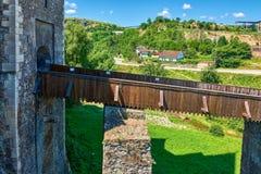 Smal fotbro över vallgraven av ett medeltida slottfort med stenväggar arkivbilder