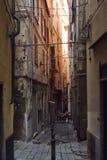 Smal gammal och mörk gata i Genoa Italy Arkivfoto