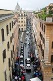 Smal gata för italienare som leder till St Peter & x27; s-basilika På gatan många bilar och personer under paraplyer Fotografering för Bildbyråer