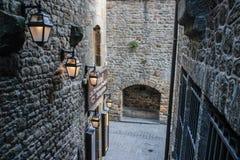 Smal gata för medeltida sten med stenhus, en båge och flera gatalampor på väggarna royaltyfria foton