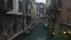 Smal gata för slags tvåsittssoffa i Venedig, folk som har partiet i litet kafé på banken av kanalen arkivfilmer