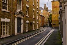 Smal gata i den gamla stilen, med tegelstenbyggnader som är historiska Arkivbilder