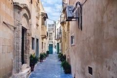 Smal gata i Rabat, Malta med bostads- byggnader på middagen Arkivbilder