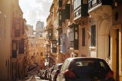 Smal gata med färgglade balkonger i historisk del av Valletta arkivbilder