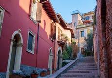 Smal gata med färgrika hus längs vägen till Castel San Pietro, Verona arkivbild