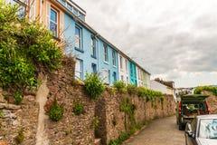 Smal gränd längs färgfasadbyggnader, högväxt stenvägg, pott Royaltyfria Foton