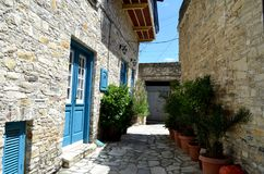 Smal grekCypern gata - vithus med den blåa dörren royaltyfria bilder