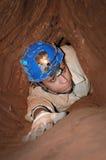 Smal grottapassage med en caver Royaltyfri Foto