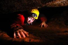 Smal grottapassage med en grottautforskare Royaltyfria Foton