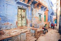 Smal indisk gata med blåtthus och rusaskolbarn i historisk stad av Indien Arkivfoton