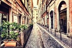 Smal italiensk gata med en hemtrevlig kaféterrass i en trendig del av Rome royaltyfria bilder