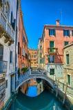 Smal kanal med bron i Venedig, Italien, HDR fotografering för bildbyråer