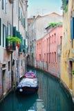Smal kanal med ett fartyg i Venedig Arkivfoto