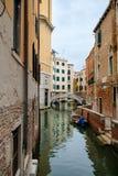 Smal kanal som omges av gamla slottar i Venedig Royaltyfria Bilder