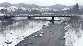 Smal ström som flödar under en bro i Carpathiansna i vinter i slo-mo arkivfilmer