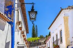 Smal vit lampa för gataslottvägg Obidos Portugal Arkivbild