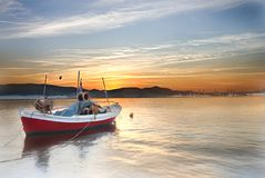 Small boat on a sea at sunset. A smal wooden boat floating with no people on the sea at sunset, Volos, Greece Stock Images