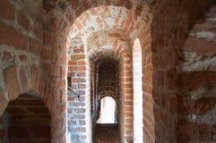 Smala gamla forntida slottkorridorer, tunneler, bågar av röda stentegelstenar i en medeltida slott arkivbilder