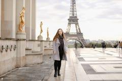 Smaling kvinnaanseende på Trocadero den fyrkantiga near förgyllda statyer och Eiffeltorn Royaltyfri Fotografi