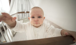 Small abandoned baby in the crib crying Stock Photo
