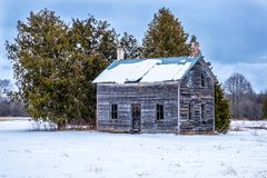 Small abandoned farm house in winter. A small delapitated wooden clad house with a steel roof sits abandoned in a field in front of some evergreen trees while stock photos
