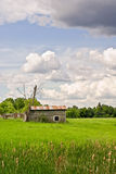 Small, Abandoned shack in the Country Side. A small, run-down, wooden shack sits alone in a lush green field in the Ottawa Valley countryside royalty free stock photography