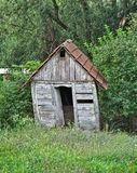 Small abandoned wooden cabin surrounded by trees Stock Images