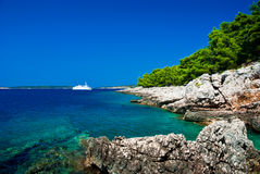 Small Adriatic island coastline. Clear azure water under blue sky. White ferry boat on background Royalty Free Stock Photo