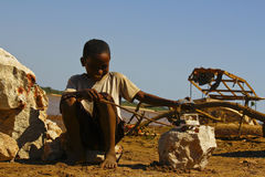 Small African boy, outdoors, playing with a car Stock Photos