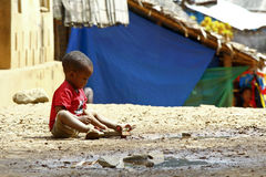 Small African boy, outdoors, playing with a car Royalty Free Stock Photography
