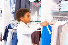 Small African boy in white shirts choosing clothes Royalty Free Stock Photography