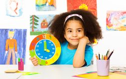 Small African girl holding showing time Stock Photo