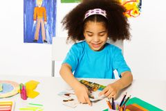 Small African girl putting puzzle pieces together. At the table while sitting in playroom with wall behind full of children drawings stock image