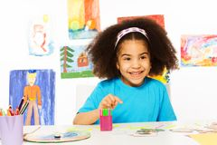 Small African girl sits at the table with puzzle stock images