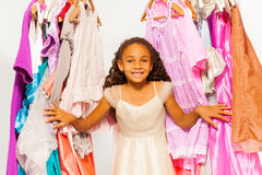 Small African girl standing between hangers. With colorful bright dresses, clothes during shopping stock image