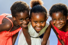 Small african girls joining heads. Close up portrait of three small happy African girls with heads together stock images