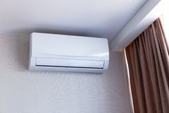 Small air conditioning on the wall inside room in apartment, switched off. Interior in calm beige tones royalty free stock photos