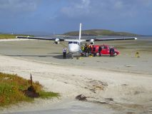 Small aircraft at beach airport. Passengers embarking on a DHC Twin Otter aircraft at the beach airport on Traigh Mhor on the isle of Barra in the Western Isles royalty free stock photo