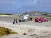 Small aircraft at beach airport. Passengers embarking on a DHC Twin Otter aircraft at the beach airport on Traigh Mhor on the isle of Barra in the Western Isles royalty free stock image